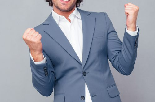 Portrait of a cheerful businessman celebrating his success over gray background